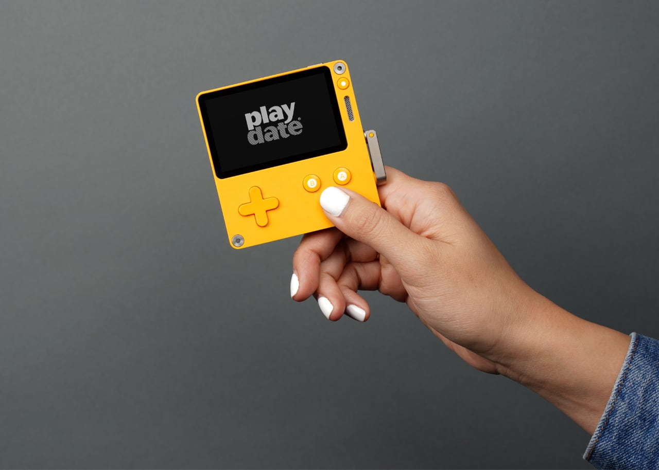 Panic's Playdate handheld console, held by a model.